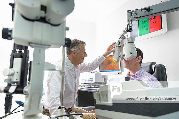 Optiker  der bei Optikern für Kleinunternehmen die Augen von Patienten misst