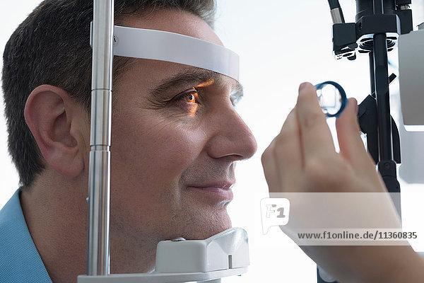 Optiker  der bei Optikern für Kleinunternehmen in die Augen des Patienten schaut