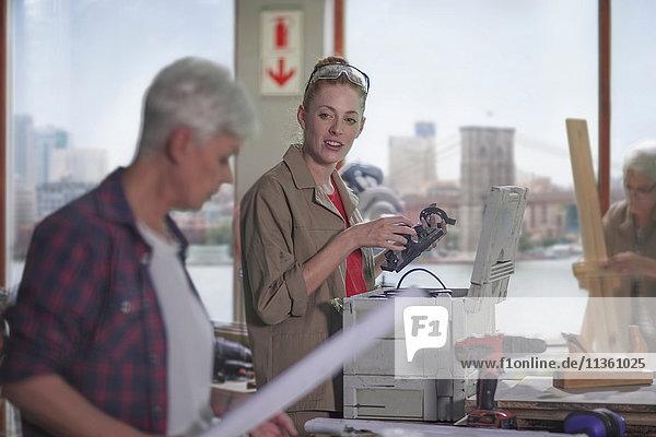 Tischlerin bespricht Ausrüstung mit Praktikantin in Möbelbauwerkstatt