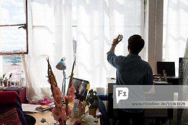 Scherenschnittansicht eines Mannes  der den Druck an einem sonnenbeschienenen Fenster im Druckmaschinenstudio hochhält