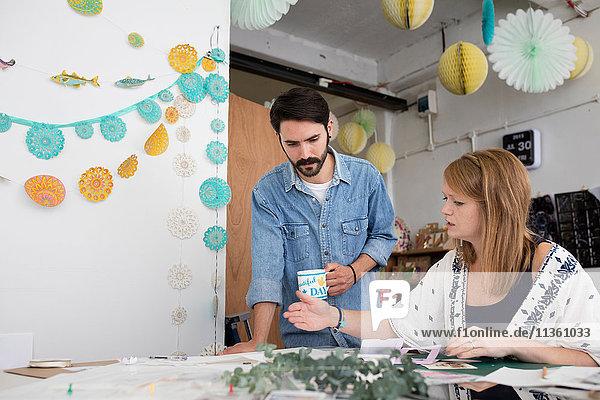 Gestalterin und Gestalter bereiten im Druckmaschinenstudio Mixed-Media-Design vor
