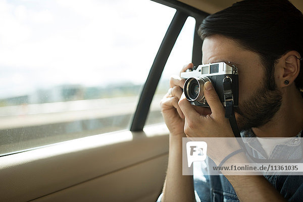 Young man on the road  taking photographs through car window