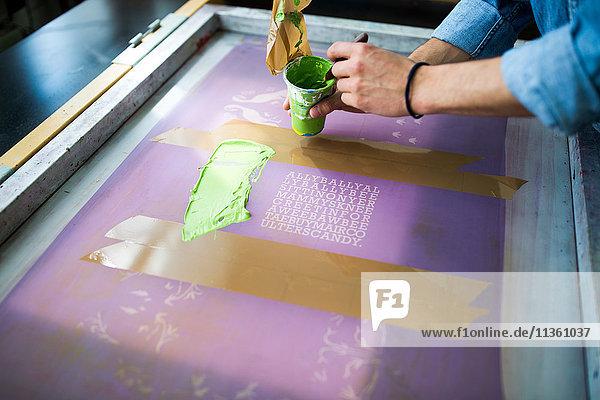 Hände eines männlichen Druckers beim Auftragen grüner Tinte auf den Siebdruck im Druckmaschinenstudio
