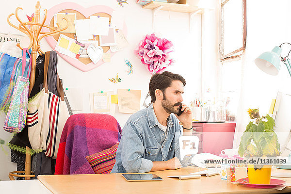 Junger männlicher Designer spricht auf Smartphone im Druckmaschinen-Studio