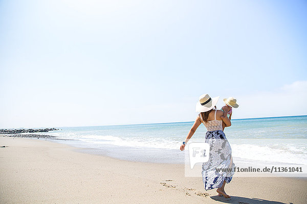Rückansicht einer Mutter  die einen kleinen Sohn am Strand trägt  Malibu  Kalifornien  USA