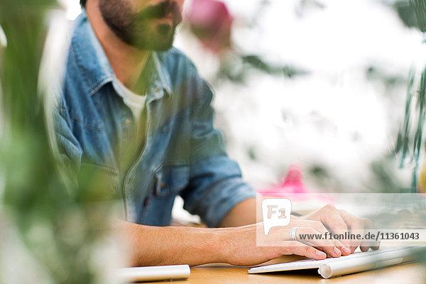 Ausschnittaufnahme eines männlichen Designers beim Tippen auf der Tastatur im Druckmaschinenstudio