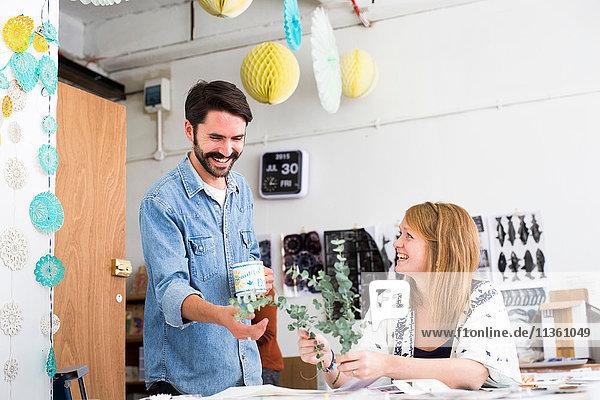 Weibliche und männliche Designer lachen über Zweigblätter im Druckmaschinenstudio