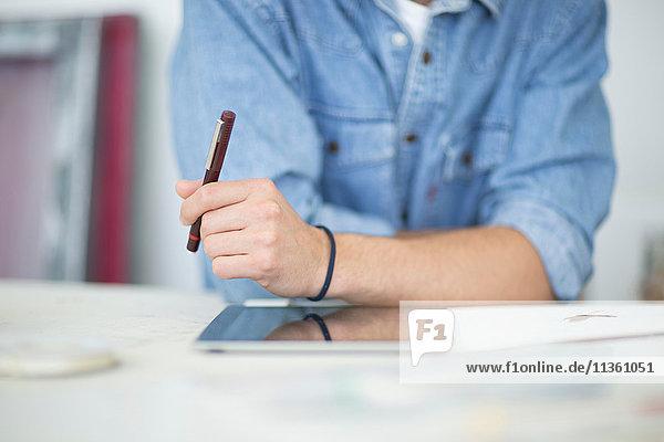 Ausschnittaufnahme eines männlichen Designers mit einem digitalen Tablett im Druckmaschinenstudio