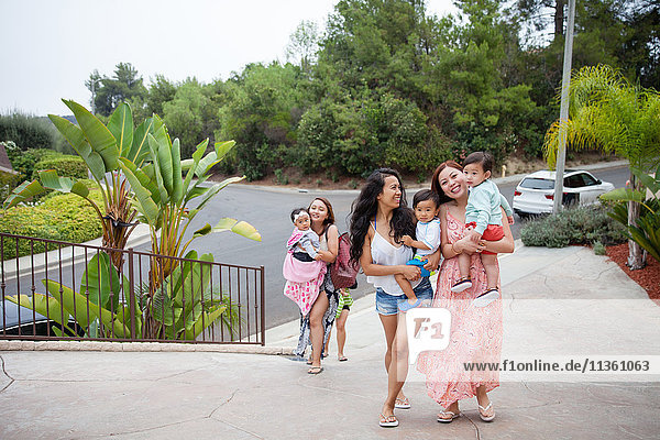Women carrying baby daughter and sons moving up driveway  Malibu  California  USA