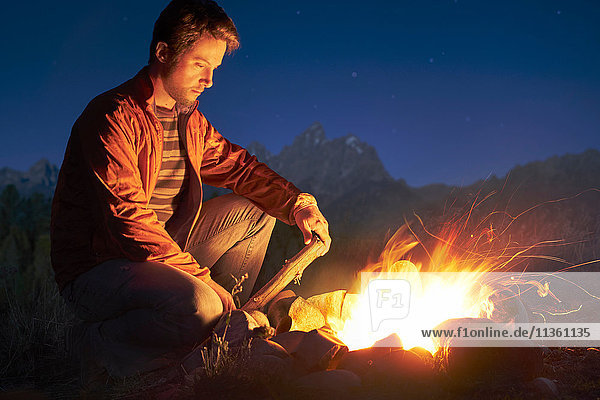 Man crouching by campfire at night  Jackson  Wyoming  USA