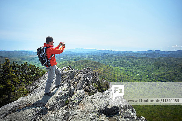 Male hiker taking smartphone photographs from ridge  Blue Ridge Mountains  North Carolina  USA