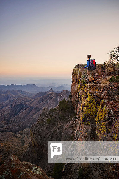 Backpacker looking out from ridge at dusk  Big Bend National Park  Texas  USA