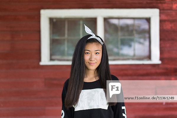 Portrait of smiling teenage girl with long black hair and hair ribbon in porch