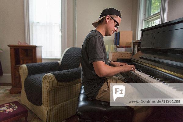 Teenager Junge sitzt im Esszimmer und spielt Klavier