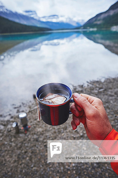 Schrägansicht eines Mannes  der am Fluss eine Tasse Tee in der Hand hält  Banff  Alberta  Kanada