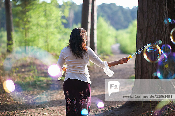 Rückansicht einer Frau im Wald beim Blasenmachen mit dem Blasenzauberstab