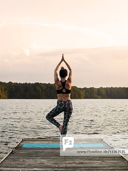 Rear view of woman on pier by lake standing on one leg in yoga position  North Carolina  USA