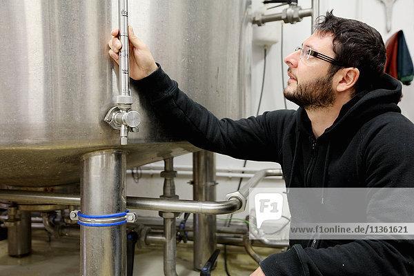 Worker in brewery  checking pressure gauge on brew tank