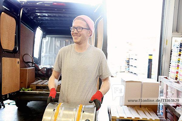 Worker in brewery  preparing to distribute barrels of beer