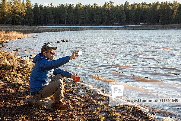 Mittelgroßer erwachsener Mann sitzt am See und fotografiert mit einem Smartphone  Flagstaff  Arizona  USA