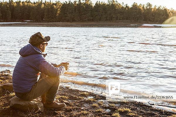 Mittelgroßer erwachsener Mann sitzt am See und schaut auf die Aussicht  Flagstaff  Arizona  USA