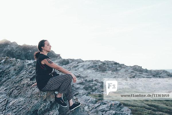 Seitenansicht einer Frau  die auf Felsen sitzt und wegschaut  Stintino  Sassari  Italien