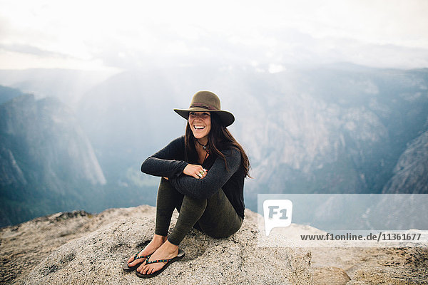 Portrait of young woman sitting at top of mountain  overlooking Yosemite National Park  California  USA