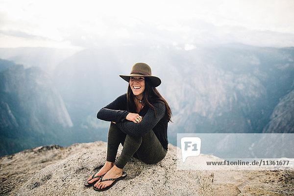 Porträt einer jungen Frau auf dem Gipfel eines Berges mit Blick auf den Yosemite-Nationalpark  Kalifornien  USA