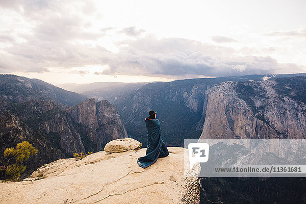 Young woman wrapped in blanket  standing at top of mountain  overlooking Yosemite National Park  California  USA