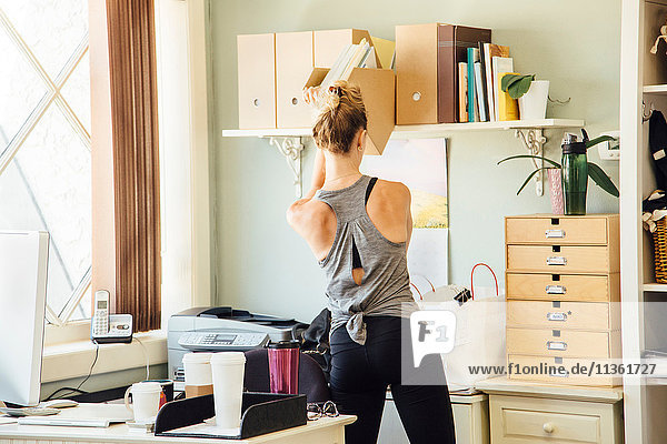 Woman in office taking paperwork from shelf