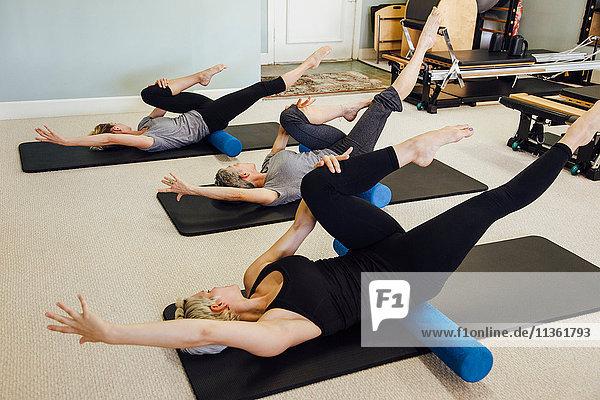 Women doing pilates on exercise mats