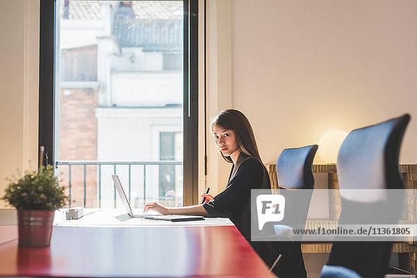 Porträt einer jungen Geschäftsfrau am Büroschreibtisch beim Tippen am Laptop
