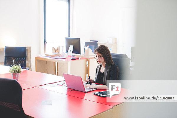 Junge Frau am Büroschreibtisch beim Tippen am Laptop