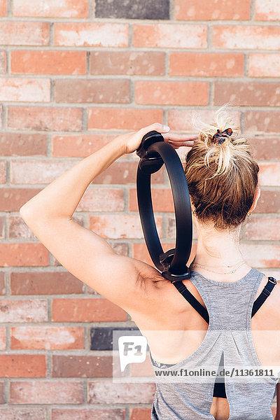 Rear view of woman using pilates toning ring
