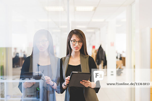 Porträt einer jungen Frau  die sich mit einem digitalen Tablett an die Bürotür lehnt
