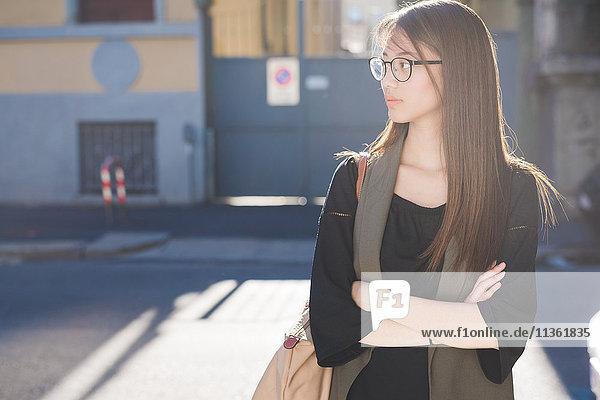 Junge Frau steht auf der Straße und schaut über ihre Schulter.