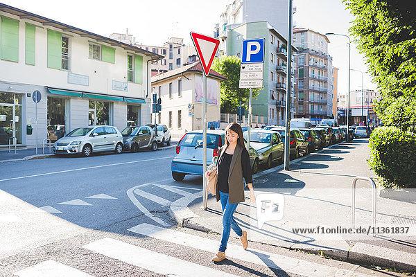 Junge Frau schlendert über den Fußgängerüberweg der Stadt