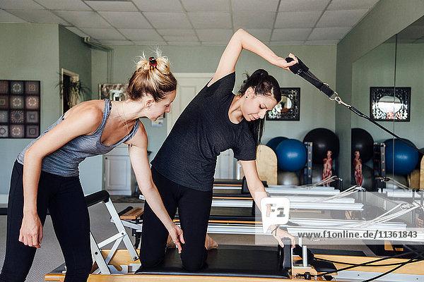 Frau und Personal Trainerin mit Pilates-Reformer