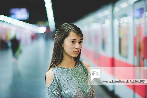 Junge Frau wartet nachts auf dem Bahnsteig auf den Zug