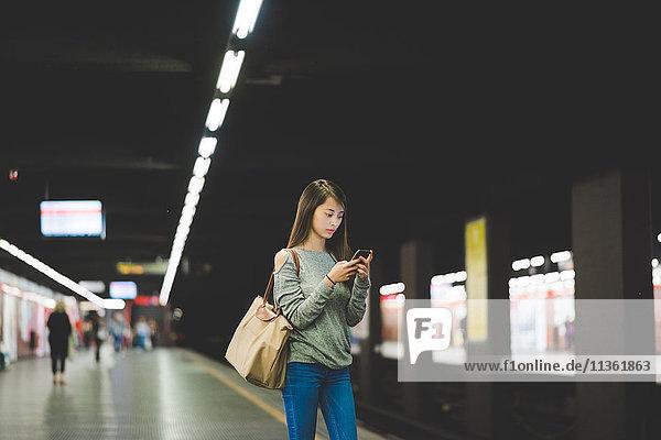 Junge Frau mit Smartphone auf dem Bahnsteig bei Nacht