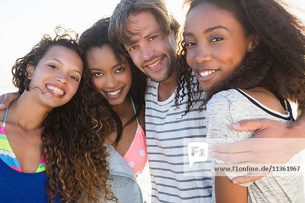 Portrait of young man and three female best friends on beach  Cape Town  South Africa
