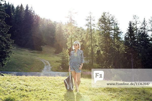 Mittlere erwachsene Frau beim Spaziergang im sonnenbeschienenen Feld  Sattelbergalm  Tirol  Österreich