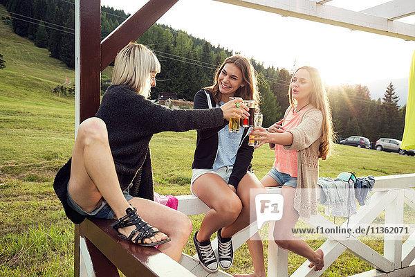 Drei erwachsene Freundinnen erheben ein Glas auf der Veranda  Sattelbergalm  Tirol  Österreich