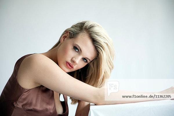 Studioporträt einer schönen blonden jungen Frau im Negligee