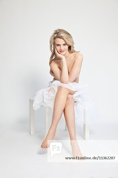 Studioporträt einer schönen  blonden  nackten  jungen Frau in Leintuch gewickelt