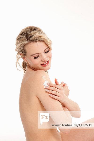 Studioaufnahme einer schönen nackten blonden jungen Frau  die Feuchtigkeitscreme auf die Schulter aufträgt