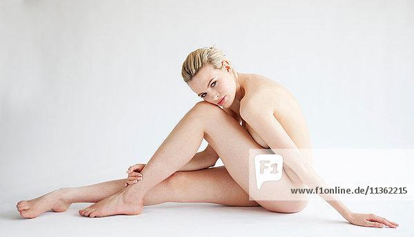 Studioporträt einer schönen nackten blonden jungen Frau  die mit dem Kopf auf dem Schoß auf dem Boden sitzt
