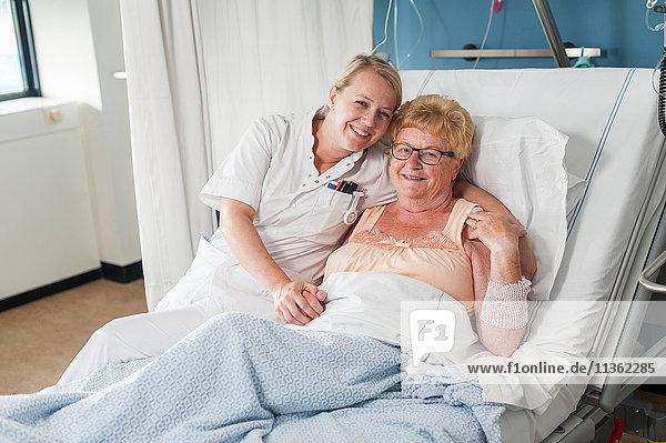 Krankenschwester und Patient auf Krankenhausbett  die lächelnd in die Kamera schauen