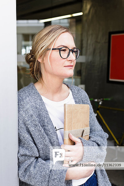 Frau hält digitales Tablet und schaut weg