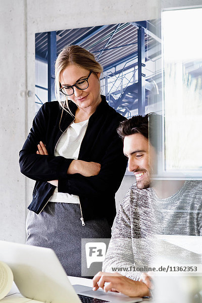 Kollegen im Büro mit Laptop lächelnd
